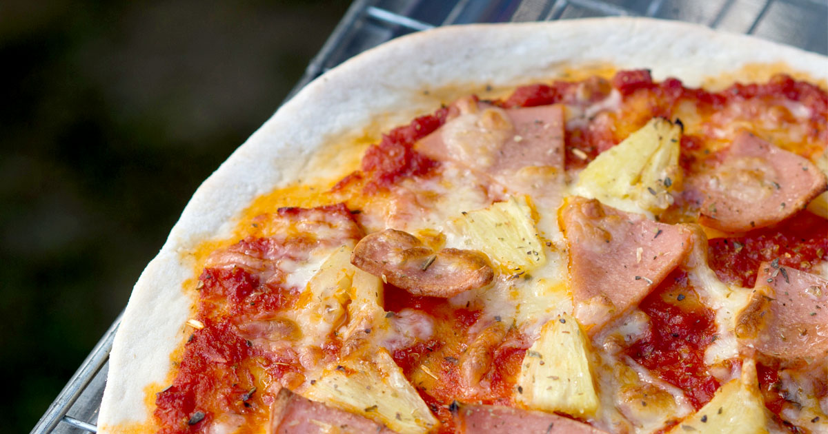 A close up of pineapple and ham pizza