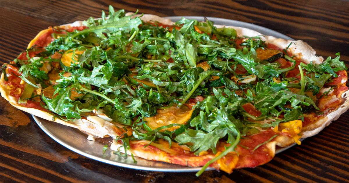 Vegan pizza topped with sauce and arugula