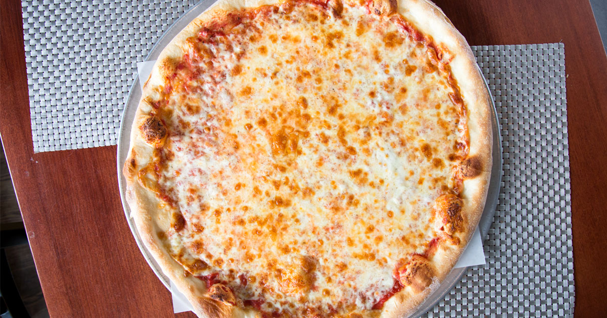A top down shot of a cheese pizza on a wood countertop