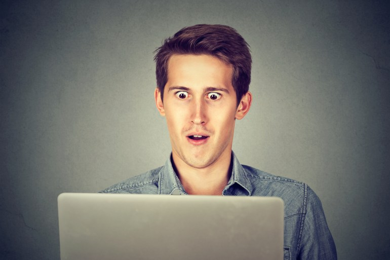 Shocked man looking at laptop