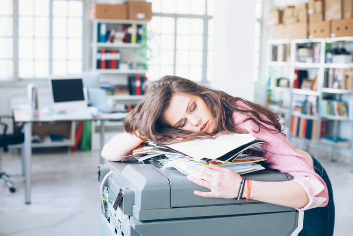 Tired and exhausted young woman sleeping on printer in the office.