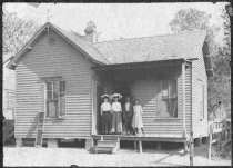 Unnamed African-American family poses for a photograph on the porch of a Dallas home, 1910