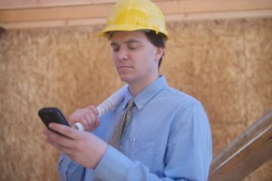 Architect Using Cell Phone With Blueprint At Site