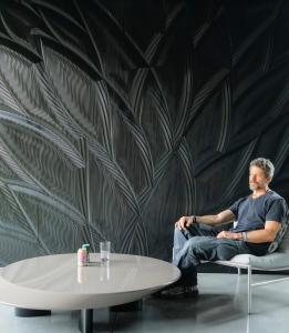 Mario Romano enjoys one of his sculptured walls made of Corian® Solid Surface