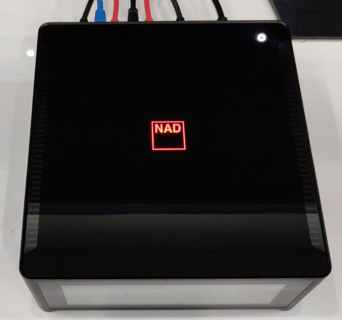 Le logo NAD sur le dessus de l'ampli s'allume en rouge à la mise sous tension avant de passer au blanc. Les ailettes des radiateurs sont visibles par transparence de chaque côté.