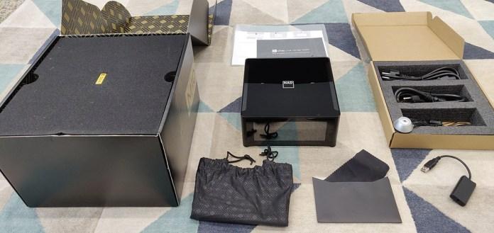 Dans son carton d'emballage, l'ampli NAD M10 est protégé par une housse. Parmi les accessoires fournis, on compte un microphone de calibration ainsi qu'un adaptateur USB vers mini-jack pour le relier à l'ampli.