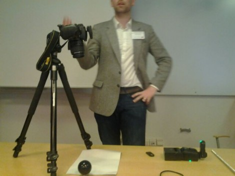 Gareth stands behind a table in a lecture room. In front of him is a camera on a tripod. The camera is set up to take a R.T.I. and so there is also a flash gun, a pool ball and a remote control on the table.