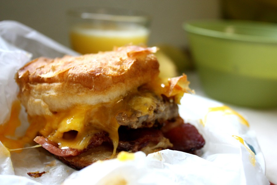 A breakfast sandwich made of golden, flaky biscuits, melted cheese, eggs, sausage, and bacon. A glass of orange juice is visible in the background.