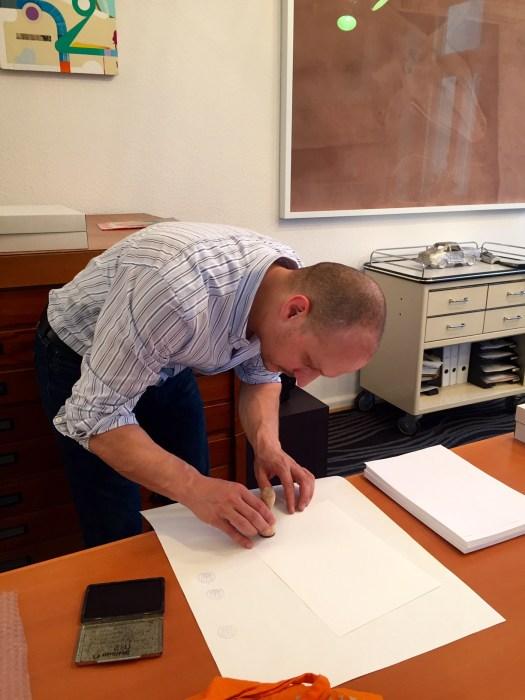 Tobias Hantmann stempelt die Zeichnungen zu seinen objekthaften Bilder mit 'Unikat X'