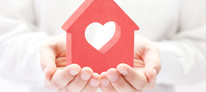Photo of hands holding a home with a heart in it.