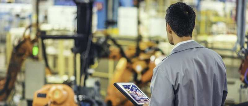 A man in a factory holding a tablet