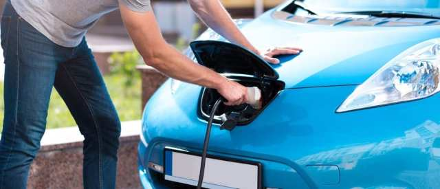 A person charging an electric car