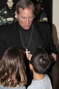 "Bishop Robert Gruss showing the Lakota (Sioux) student's his ""bling-bling""."