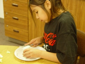 Kara is carving her soap into a Native American pipe.