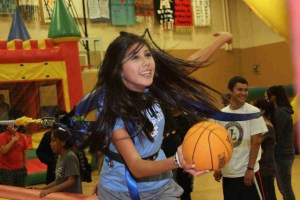 Grace tries to make a basket on the Extreme Sports Challenge during the inflatable party.