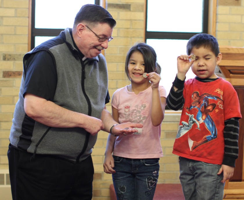 Fr. Anthony rewards the Lakota children for questions answered correctly during Mass.