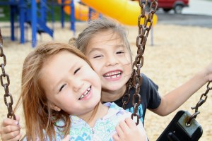 Two young girls play on the playground