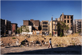 Photo: Unidentified Person Walking by a Vacant Lot with Abandoned Buildings in the Background