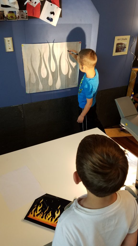 child using technology to explore projected image