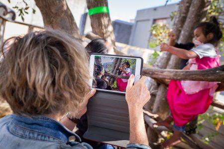 teacher taking photo of children on ipad