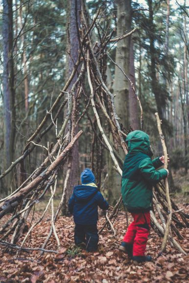 young children building a fort in nature