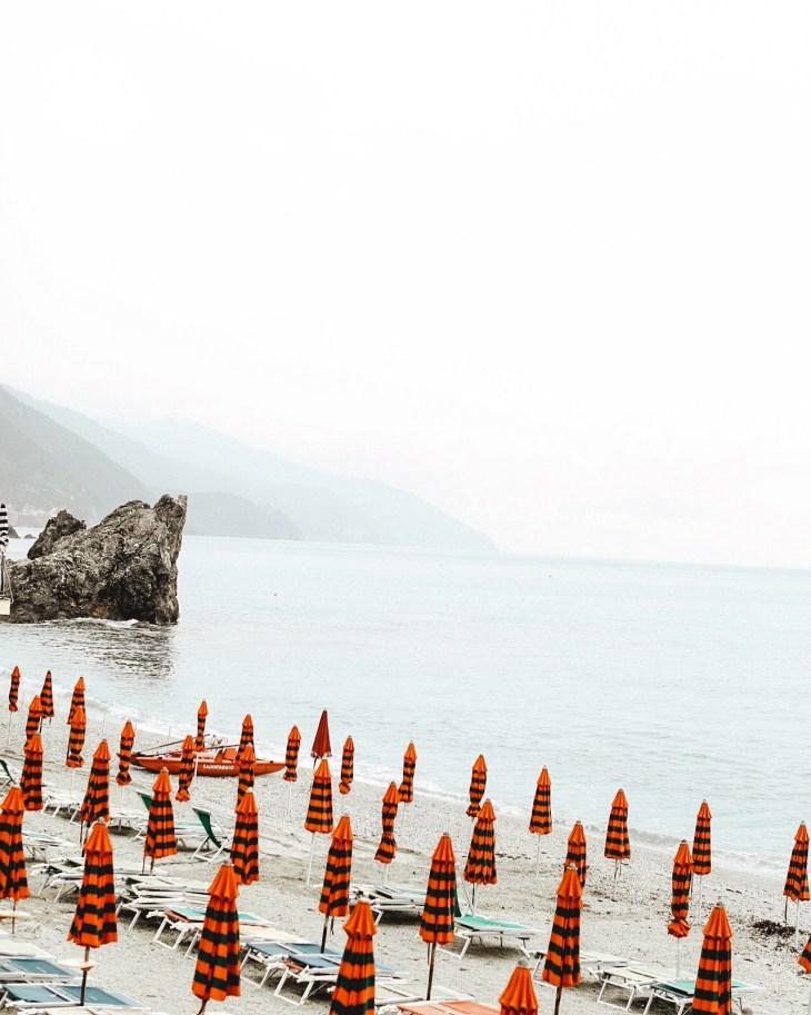 red umbrellas on beach in cinque terre