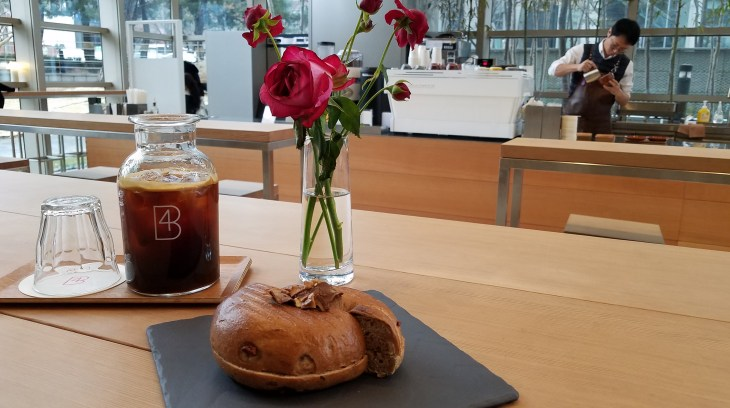 Table in coffee shop - bagel and container of coffee