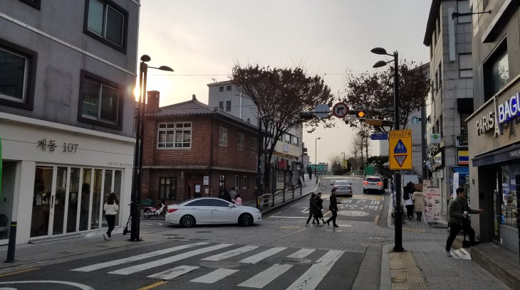 Korean street - several people crossing a street. A white car is turning.