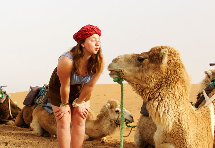 Student making a kissing face towards a camel in Fez, Morrocco