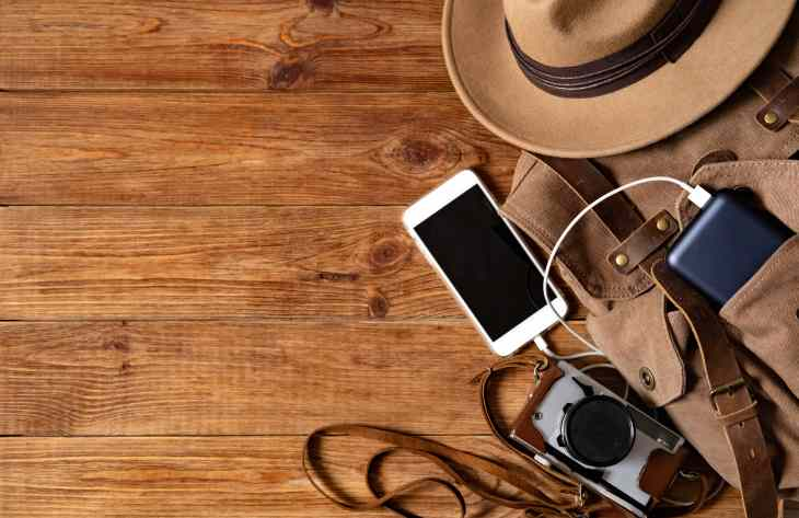 Phone plugged into portable charger that in a bag. Laing on wooden floor with hat and camera