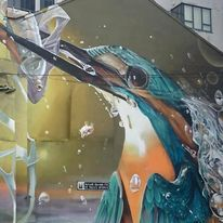 Mural of bird catching fish painted on side of building
