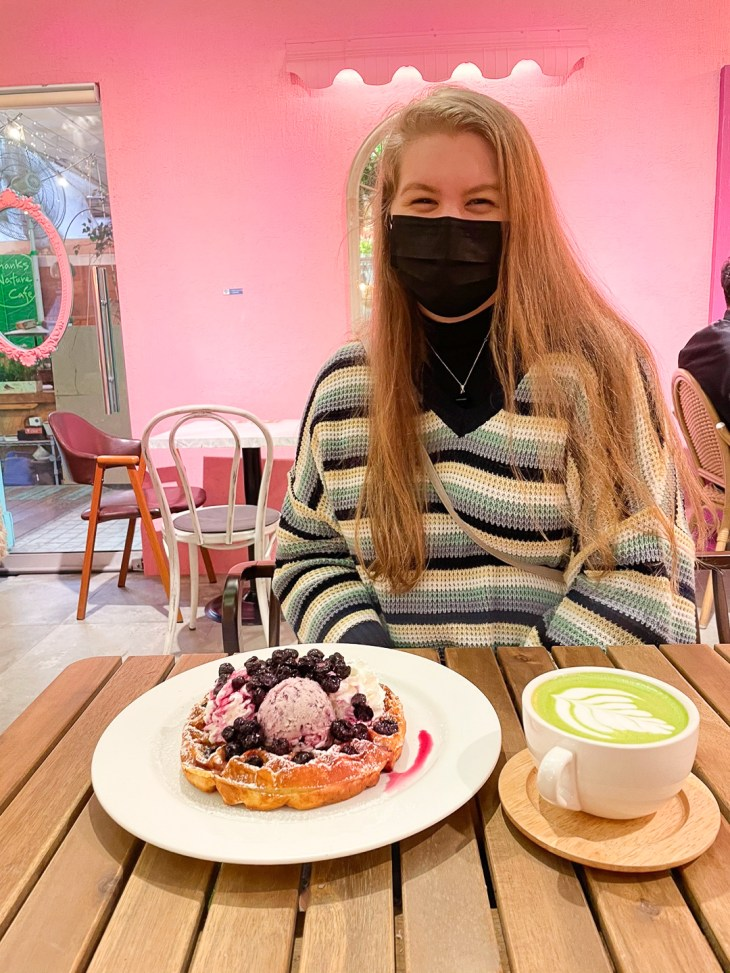 Girl wearing mask, sitting at table with waffle covered in ice cream and berries, and green tea latte in a mug