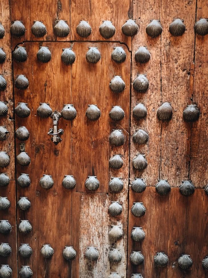 Wooden door decorated with metal seashells