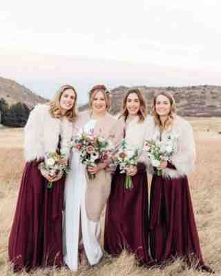 a bride with her bridesmaids wearing burgundy bridesmaids dresses for her winter wedding