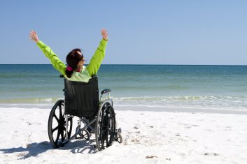 image of woman in wheelchair on beach with arms raised in victory