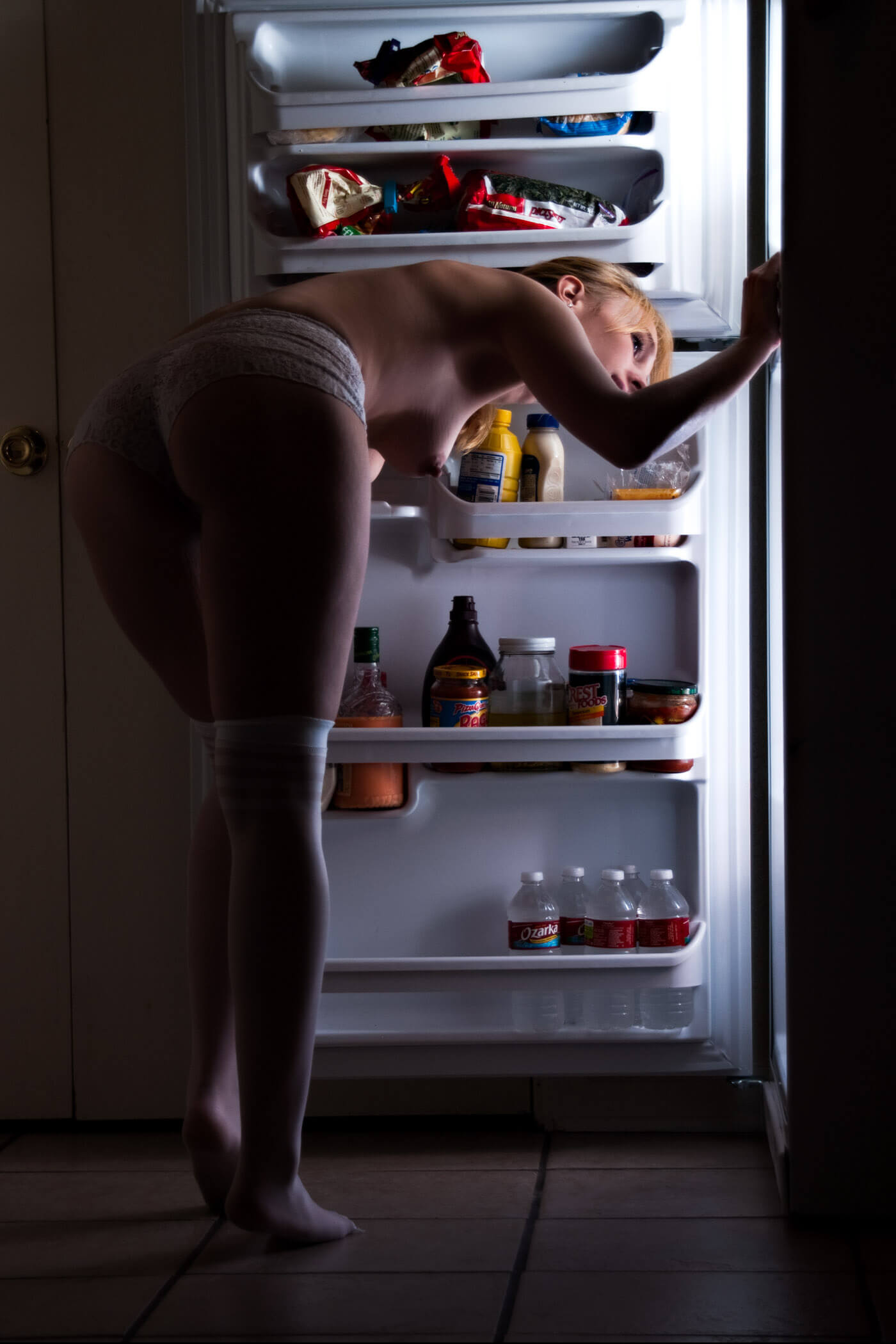 Kat standing topless near the fridge