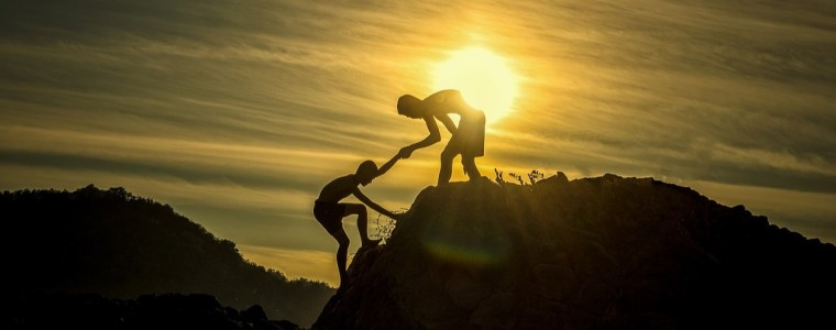 Silhouette of one person helping another person up a hill