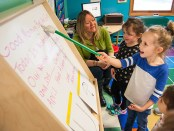 Child Pointing at Board while Teacher Looks On