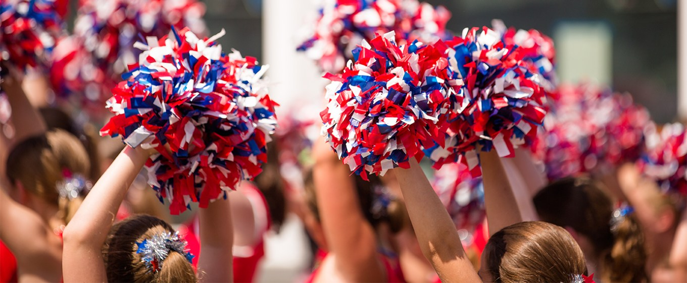 cheerleaders with poms at a parade.