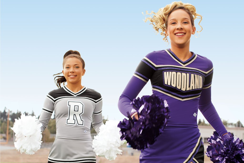 Cheerleaders with purple and white poms running across the football field
