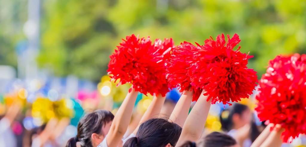 Cheerleaders shaking poms during a parade