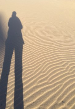 A woman's shadow on sand.