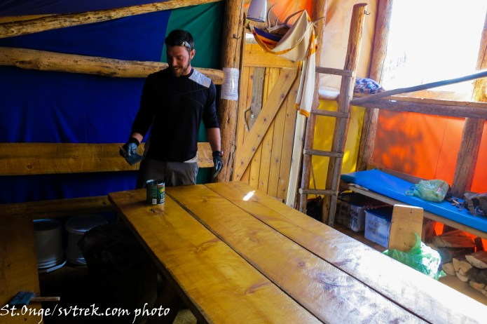 Toby, giving little love to the hand-hewn table at Fishhook Yurt