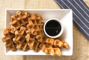 churros in a white dish with chocolate