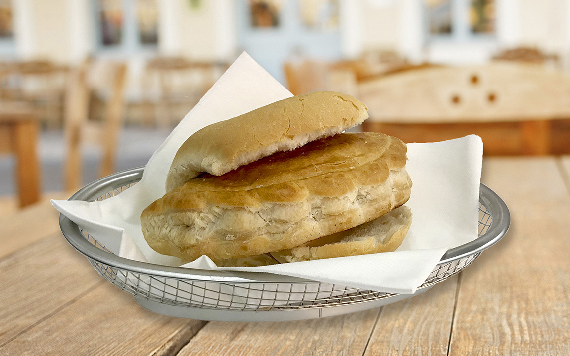 Bread roll with meat and potato pasty filling in stainless steel basket