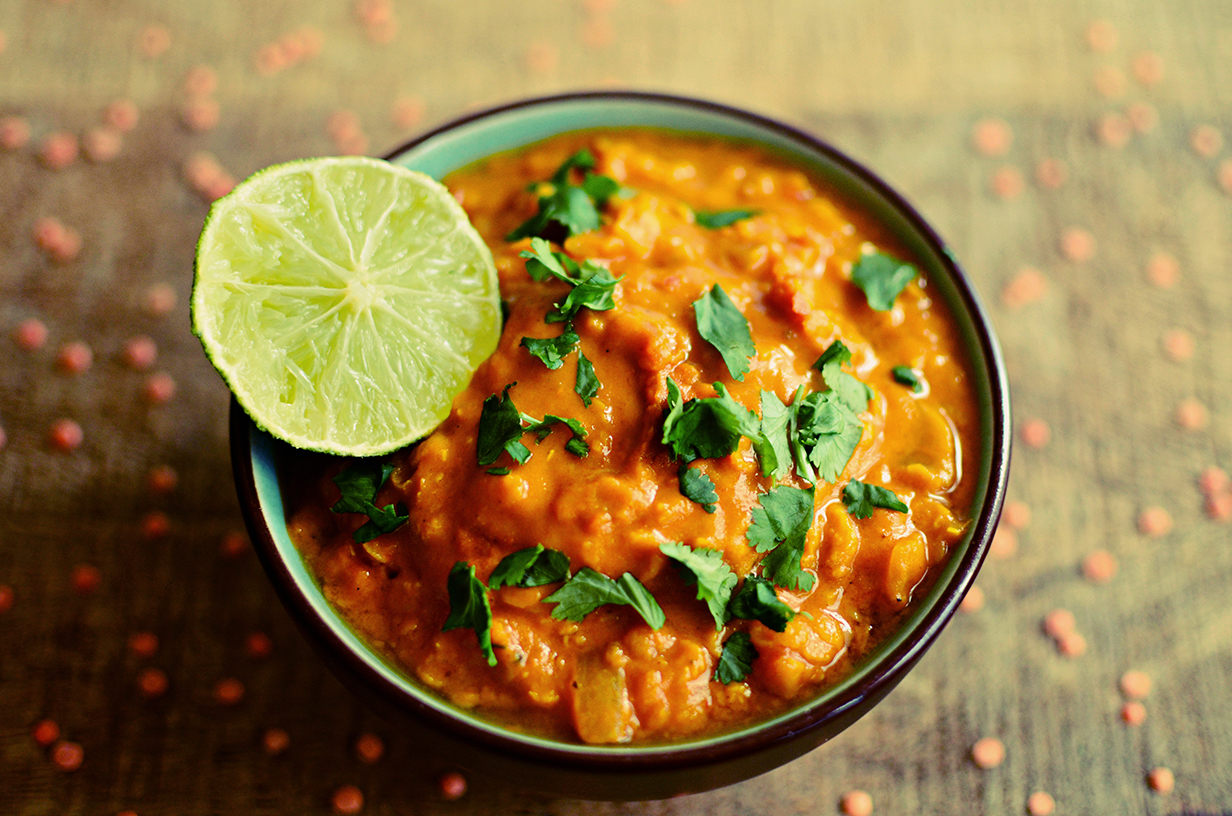 Red lentils dahl bowl with fresh lime and coriander leaves, wooden board