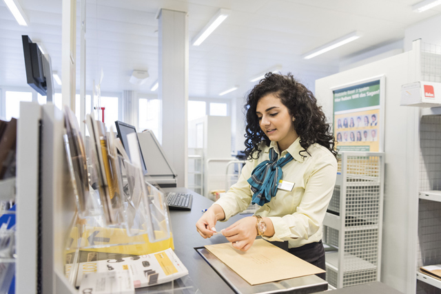 A retail trade apprentice of the Swiss Post places a stamp on a letter at the post office Basel 3 Spalen, Switzerland, on January 18, 2016. (KEYSTONE/Christian Beutler)