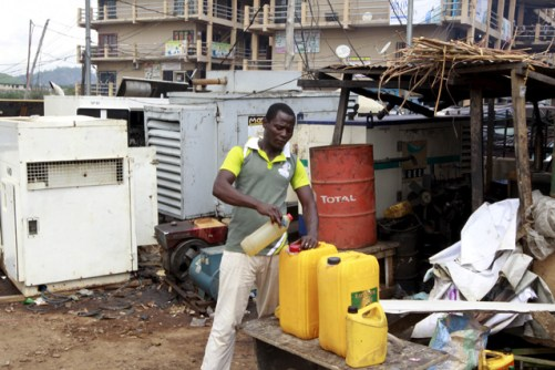 A man seen pouring diesel into a container next to power generators at the Area 10 shopping centre in Abuja, Nigeria May 25, 2015. REUTERS/Afolabi Sotunde - RTX1EGZ8