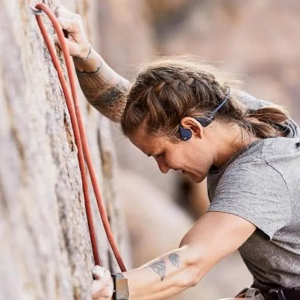Woman rock climbing with Aftershokz wireless headphones