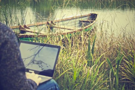 person working on laptop by a river